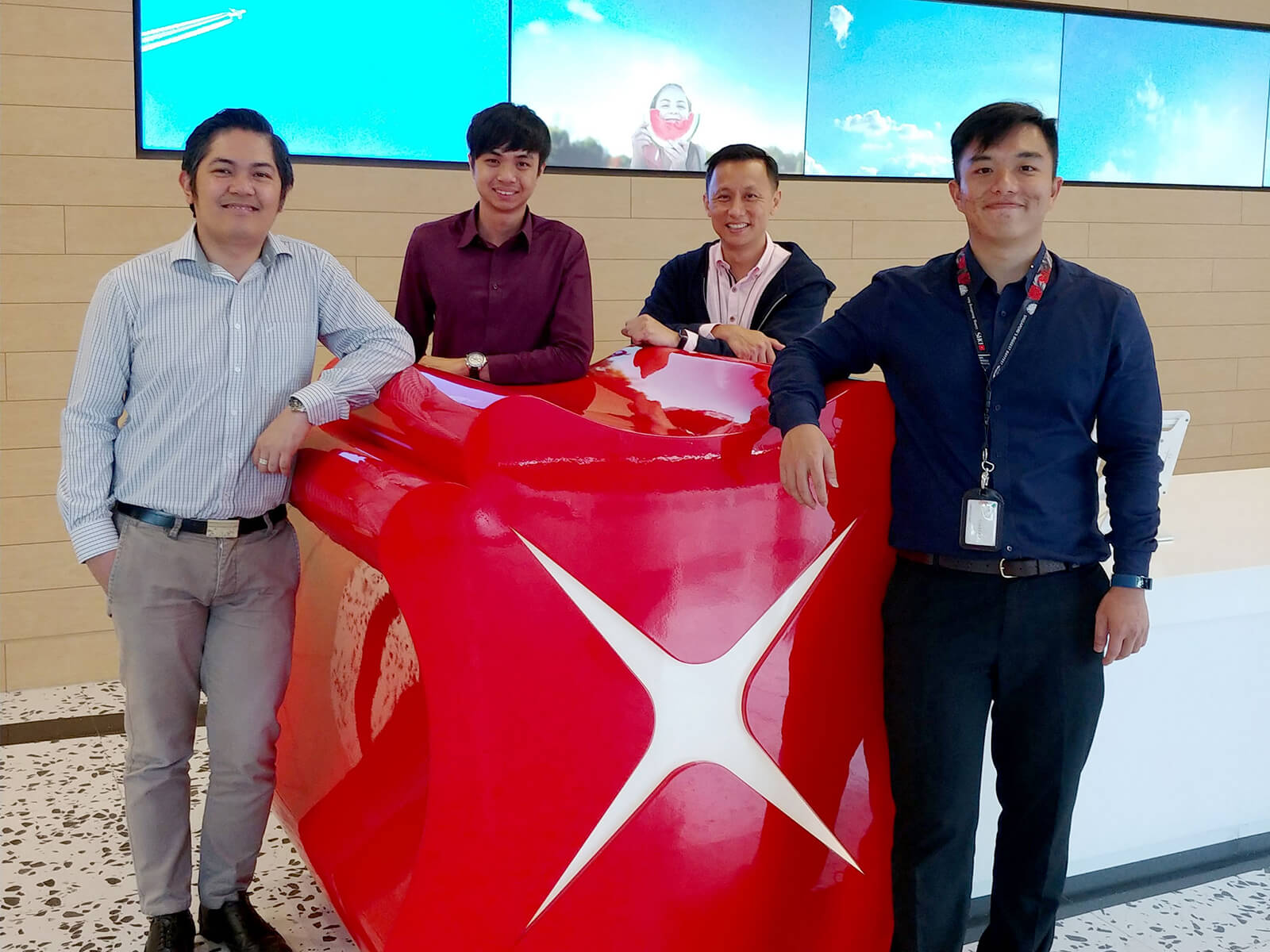 DigiPen Singapore alumni Izak Foong and Farris Chua pose with co-workers in DBS Bank lobby