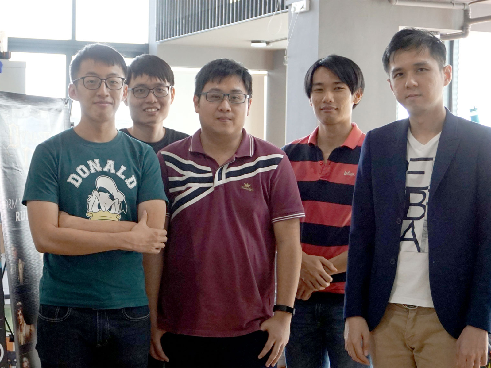 A group of DigiPen (Singapore) alumni pose next to a banner advertising the ORCA Integrated Business Operating System