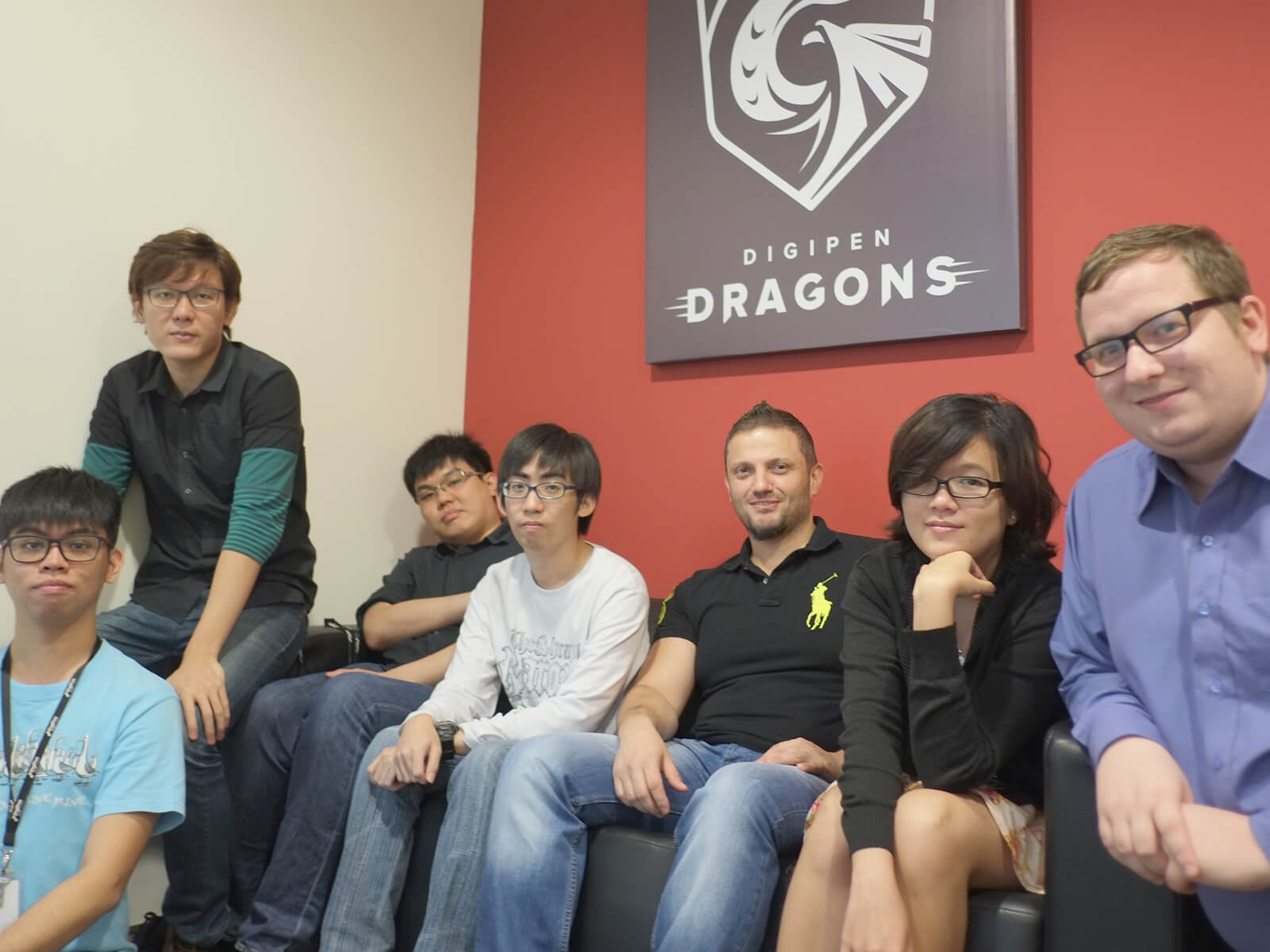 Members of the DigiPen (Singapore) Research and Development team sit at a coach below a poster of the DigiPen Dragons logo