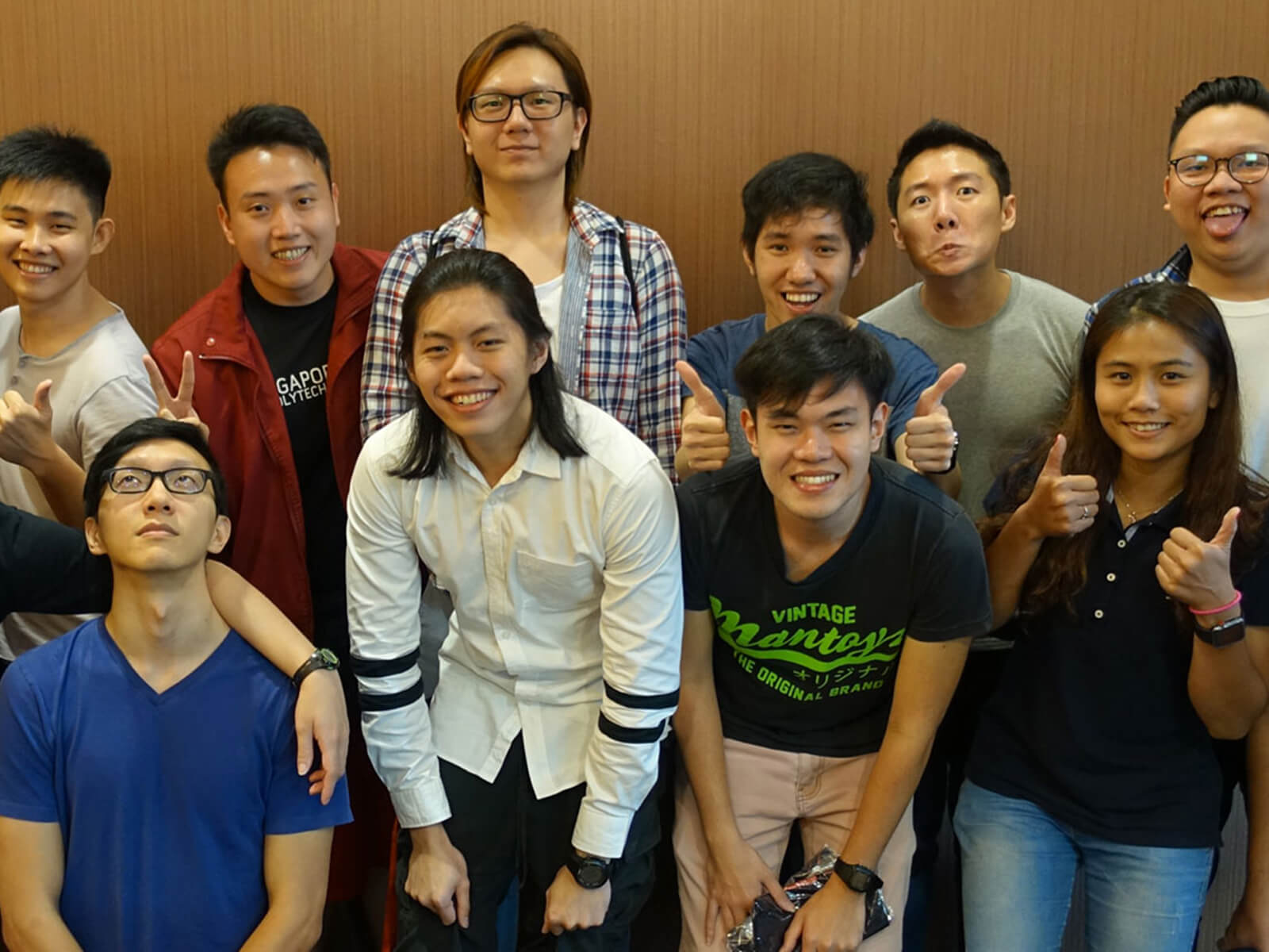 A large group of DigiPen (Singapore) Student Ambassadors smile for the camera, flashing peace and thumbs-up signs