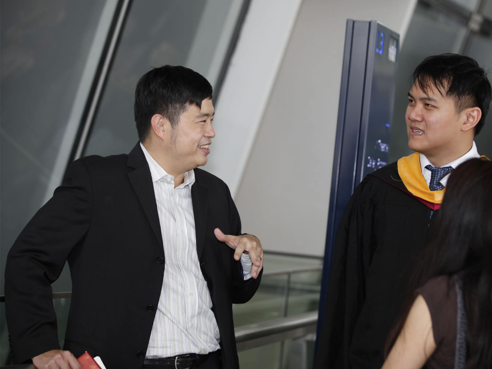 Dr. Edward Sim talks to a newly graduated DigiPen student who is wearing a cap and gown