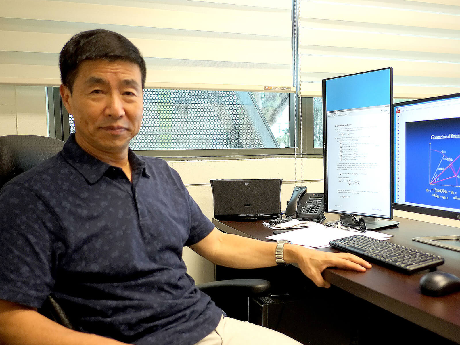 Dr. Xin Li poses for a photo at his desk which has one vertical and one horizontal monitor