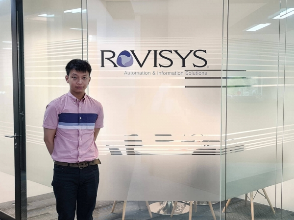 Jacky Chan standing in front of glass meeting room with Rovisys logo