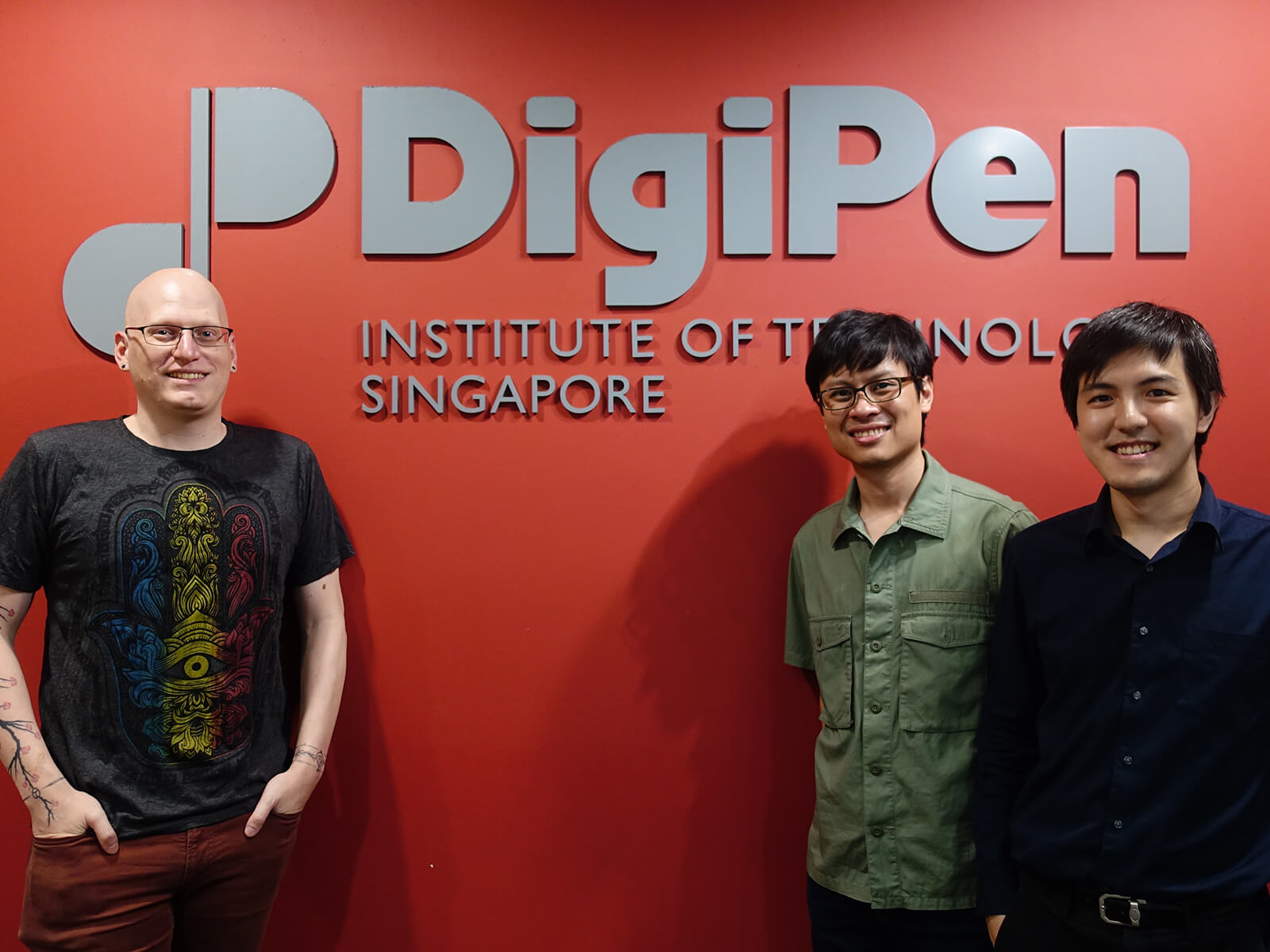Kevin Prior, Howard Sin, and Gerald Wong stand in front of a red wall with the DigiPen Institute of Technology Singapore logo