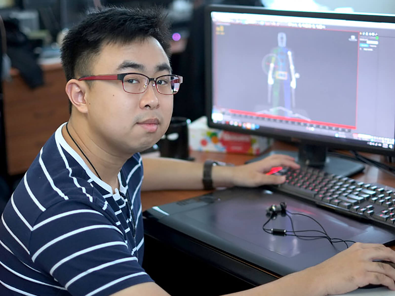 DigiPen graduate Lauri Gui poses for a photo at a desk with a monitor and tablet