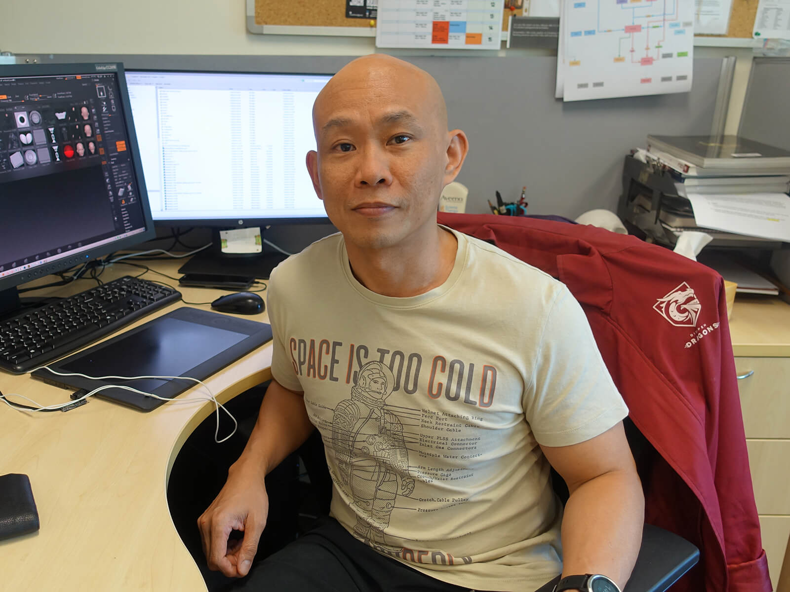Professor Marc Tan, wearing a tan T-shirt, faces the camera while sitting at his office desk; computer monitor shows thumbnails of his 3D artwork.