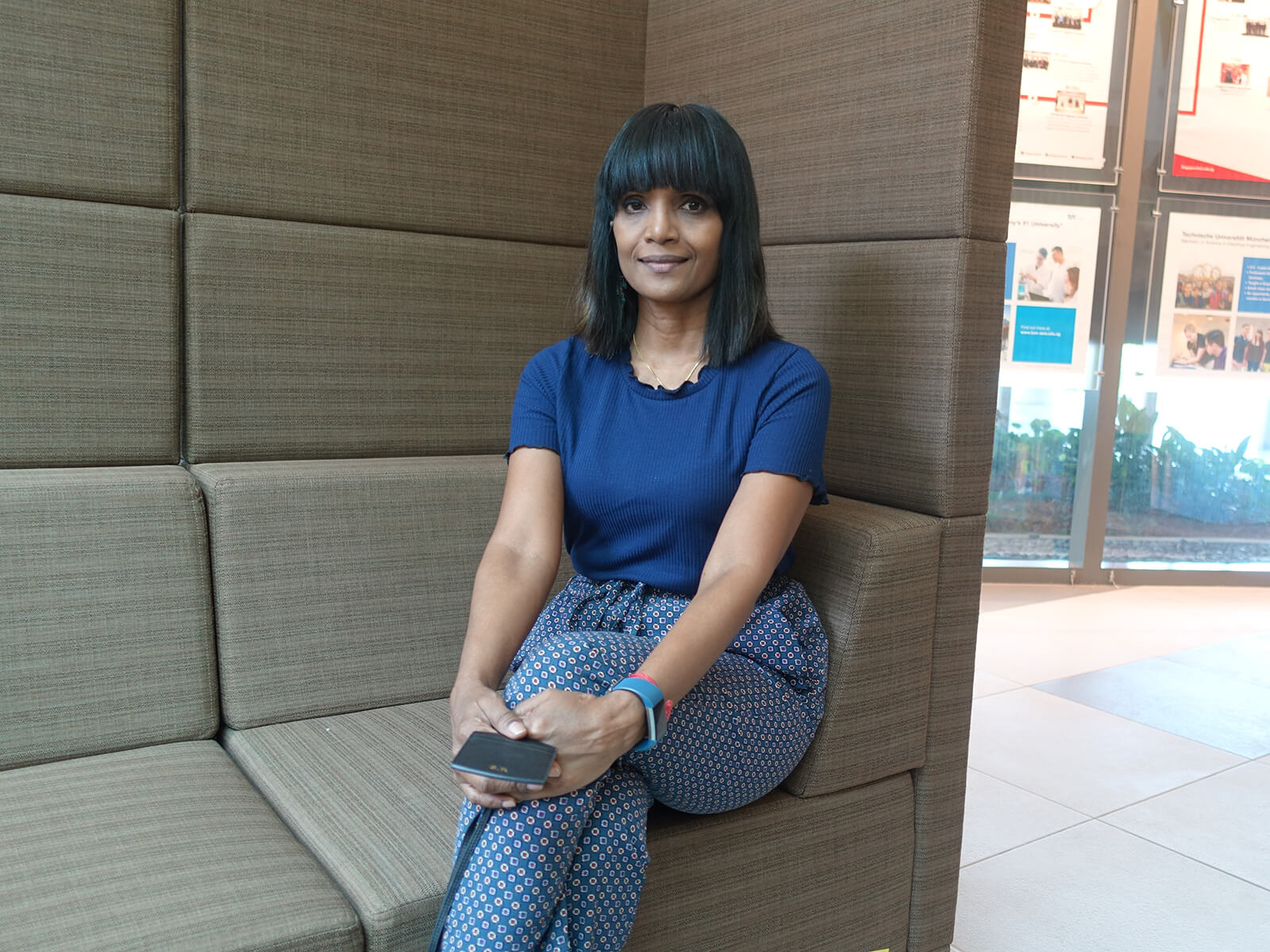Shanthina Ravindran sits on a gray sofa at the DigiPen (Singapore) campus.