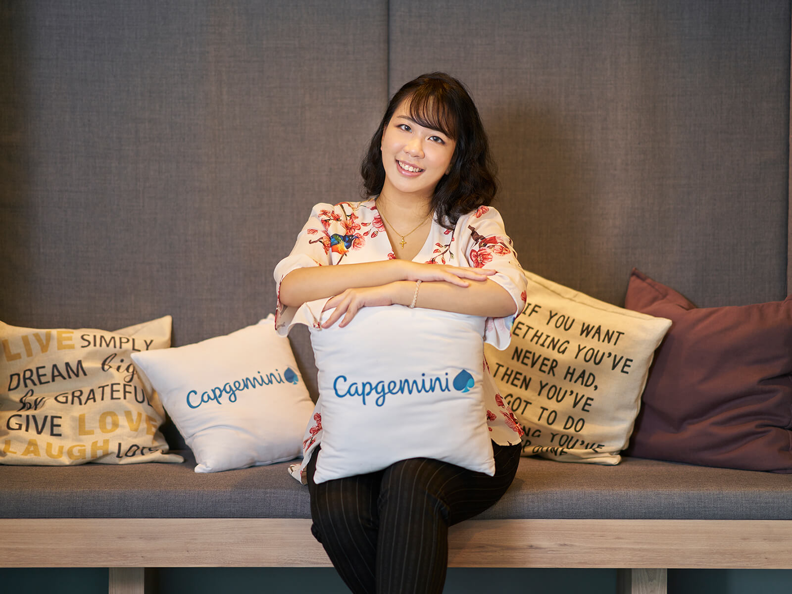 DigiPen (Singapore) graduate Sherilyn Kan smiles in an alcove with pillows