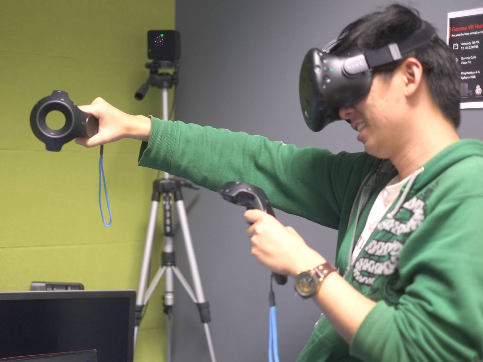 Side view of DigiPen graduate Sim Wei Jin using a VR headset and extending his right arm while using hand-motion controls