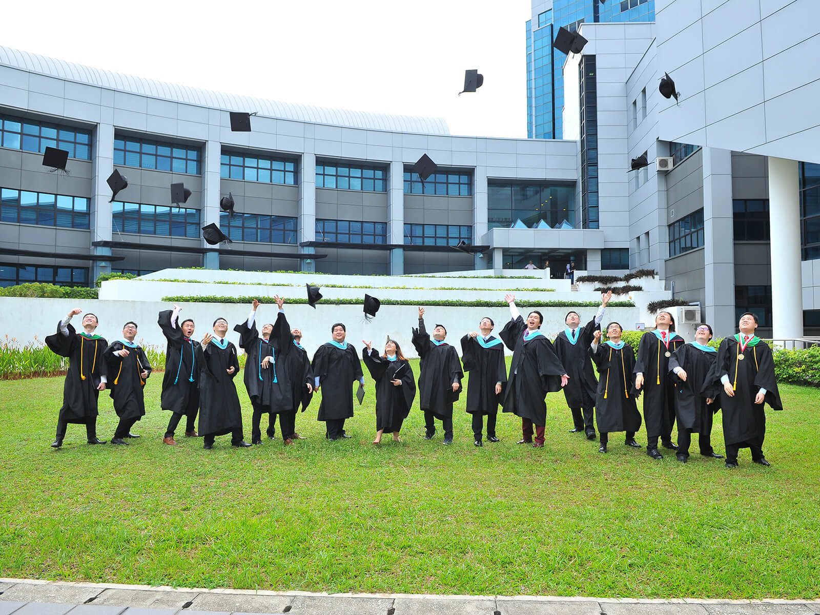 Several lined-up graduates throw their graduation caps into the air while standing outside on the grass.