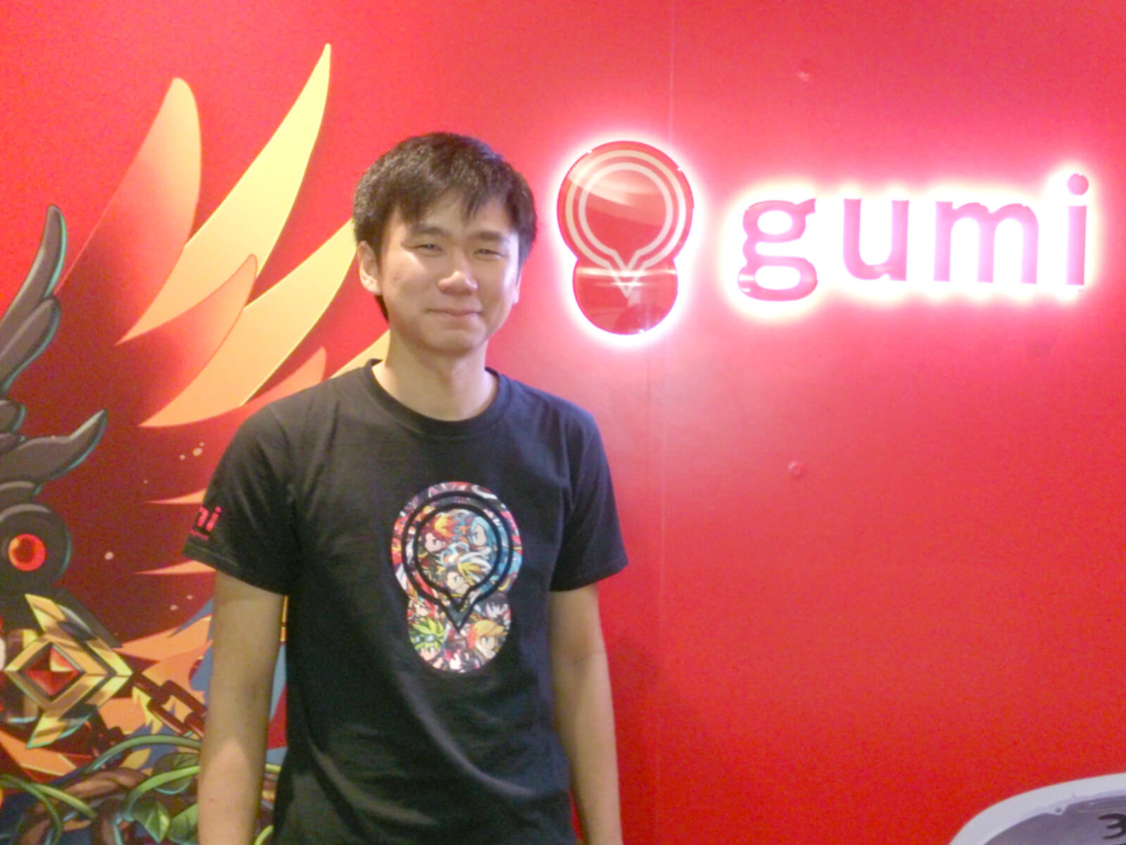 DigiPen graduate Soh Huajin stands in front of a red wall with a glowing logo for gumi Asia behind him