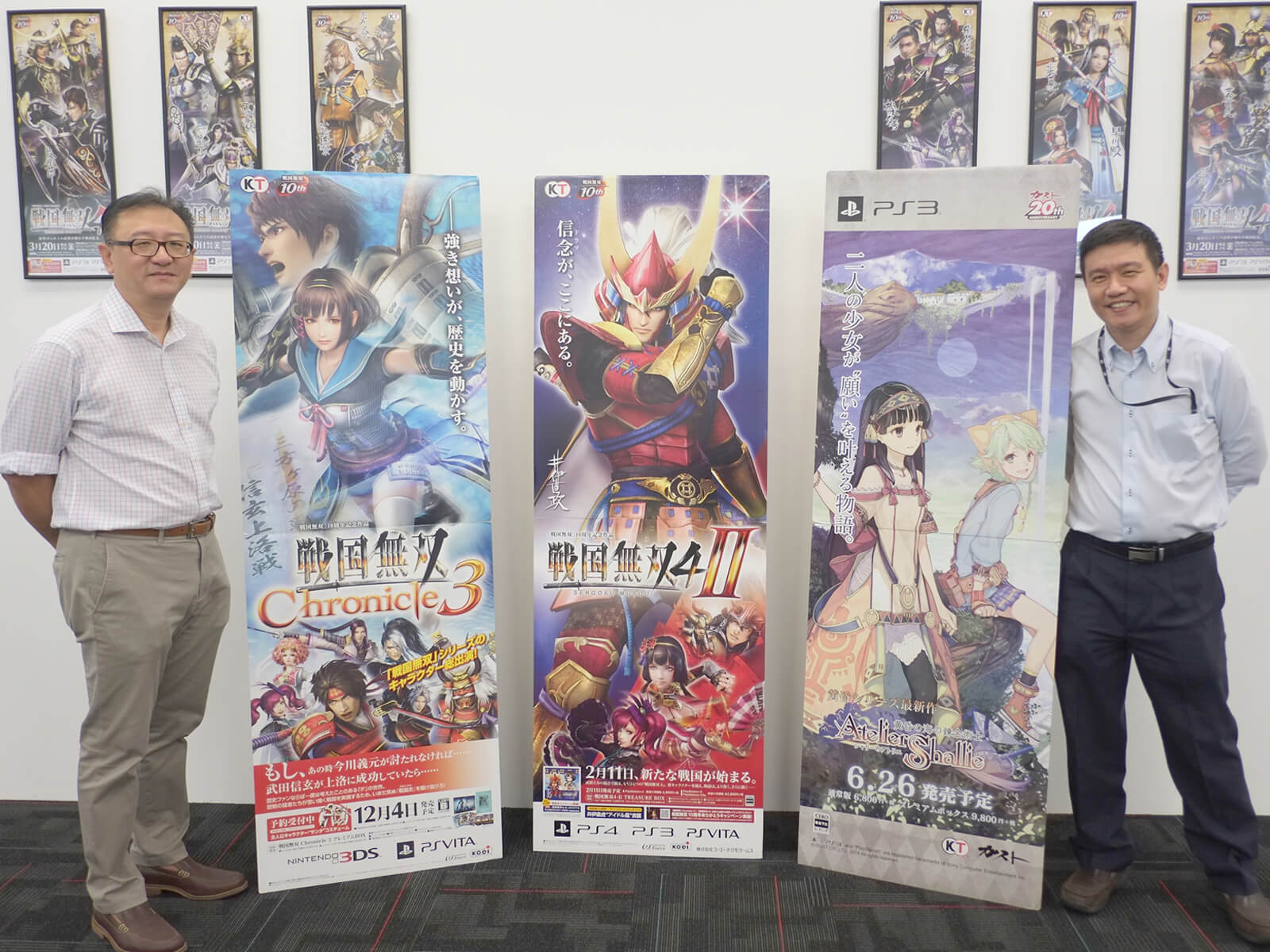 DigiPen (Singapore) representatives stand with vertical banners displaying Koei Tecmo video game titles