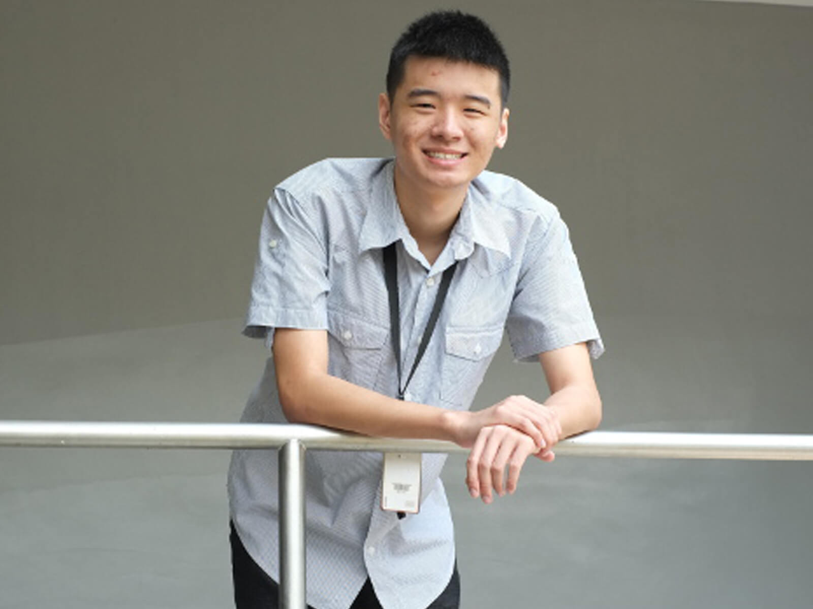 DigiPen (Singapore) student Tan Yao Wei leans on a metal railing posing for a photo