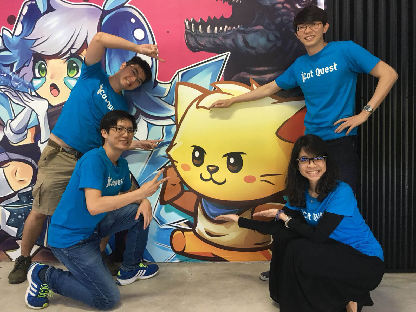 Four Gentlebros team members wearing Cat Quest T-shirts pose in front of a Cat Quest backdrop.