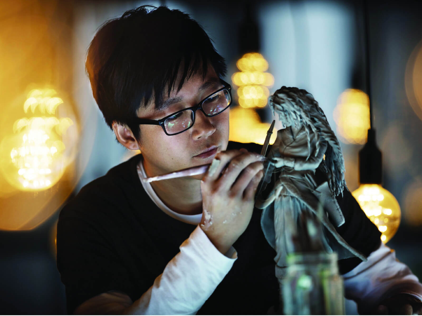 Male student carefully sculpting a detailed female clay statue