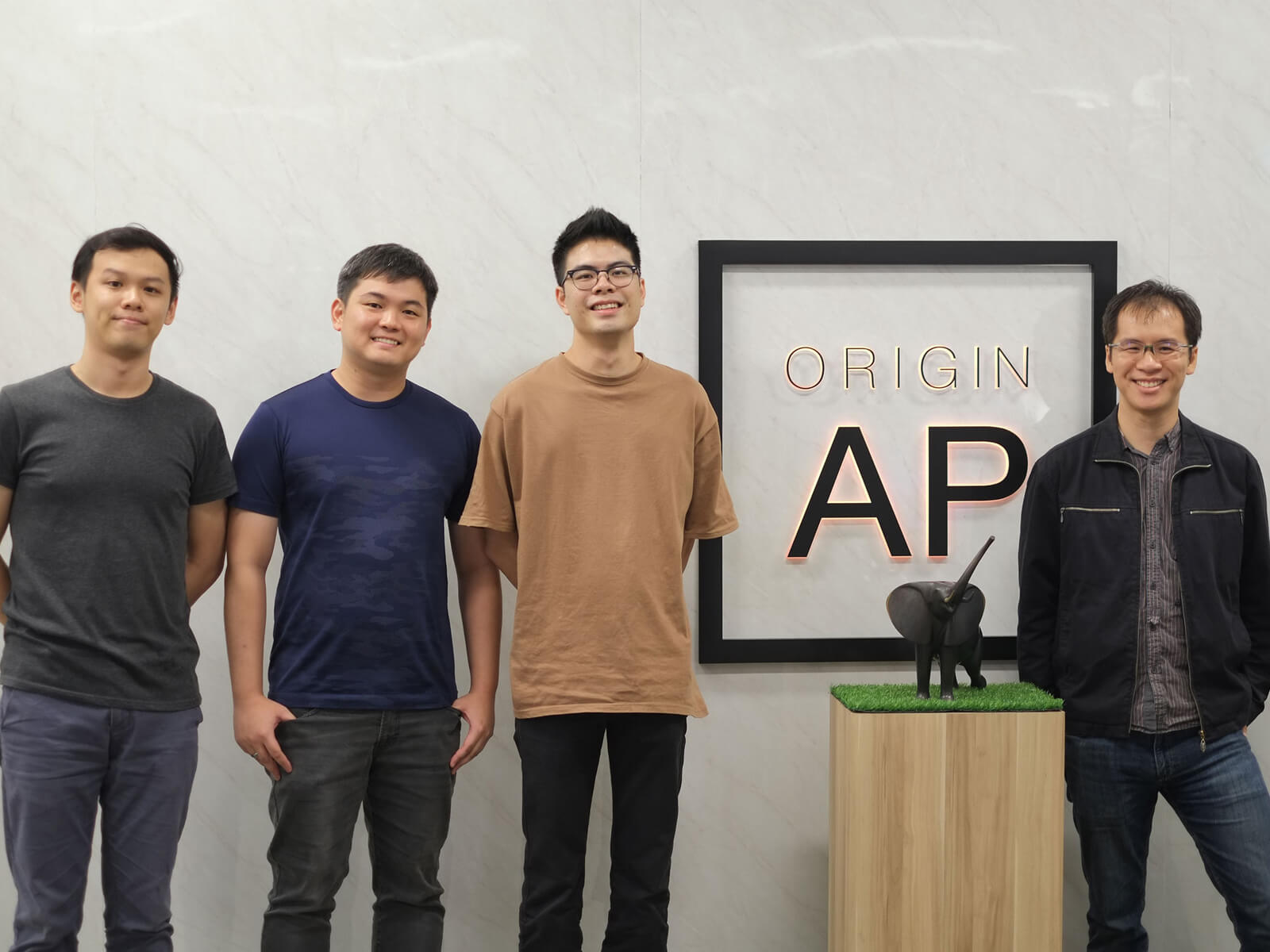 DigiPen alumni stand against a white marble wall with the Origin A P logo between them