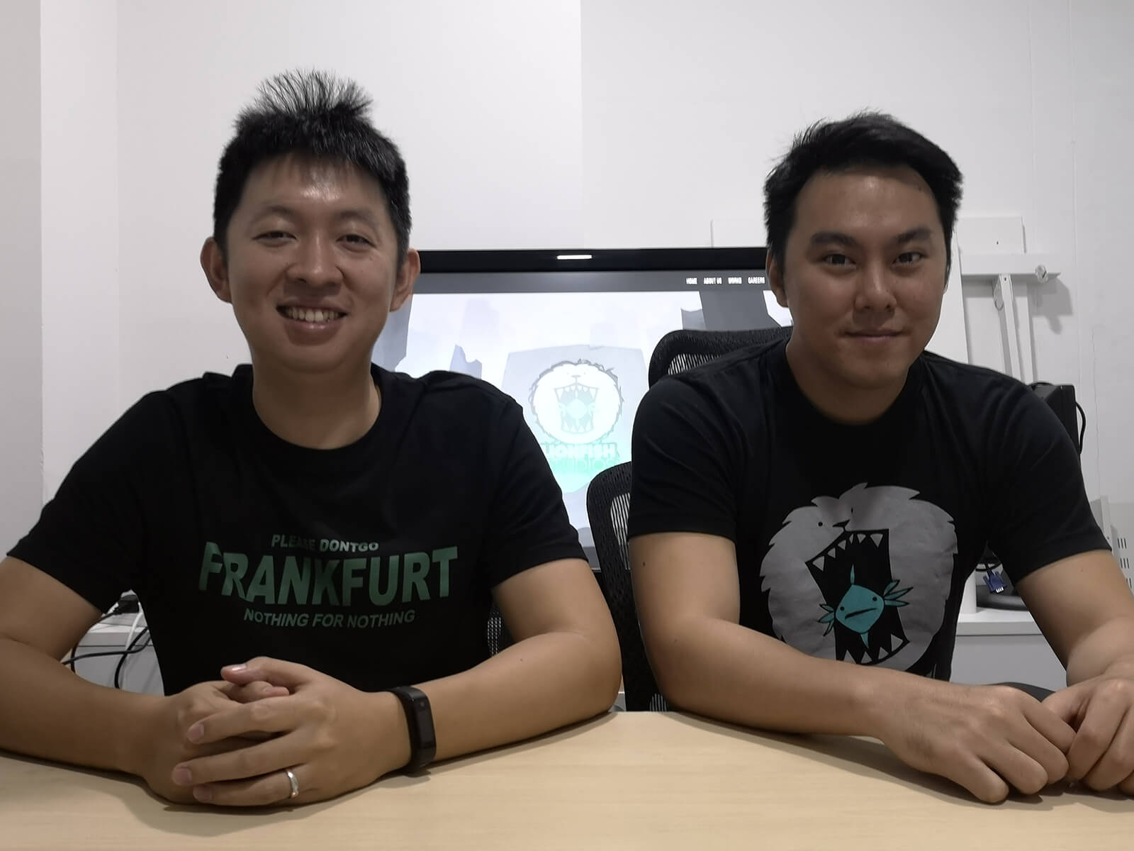 DigiPen (Singapore) alumni Zhang Zi Tian and Koh Shi Xiang sit in the office of Lionfish Studios, which they co-founded