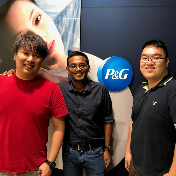 Two SIT-DigiPen (Singapore) graduates stand in front of the Procter & Gamble company logo