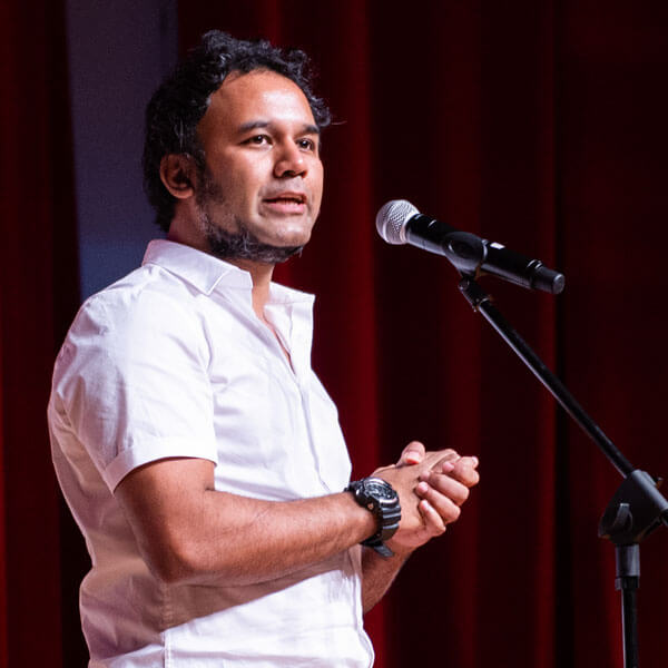 Rahul Nath stands before a microphone.