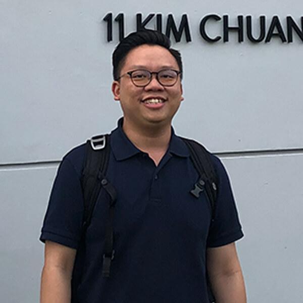 "Samuel Tan stands in front of the 'SMRT Trains Ltd. - Kim Chuan Depot"" sign."
