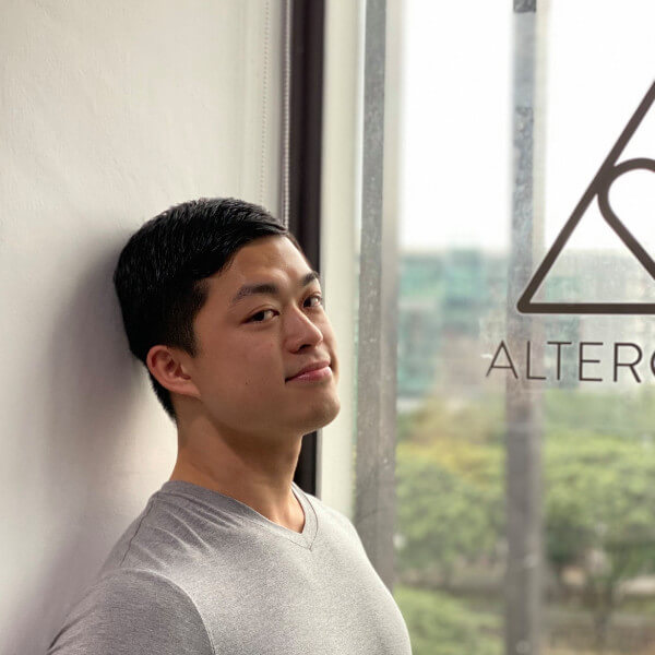 Jedidiah Siah resting against wall with AlterCulture logo on window