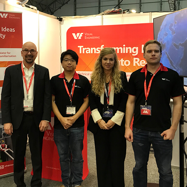 4 Visual Engineering employees stand parallel together facing camera in front of a company booth at an expo event.