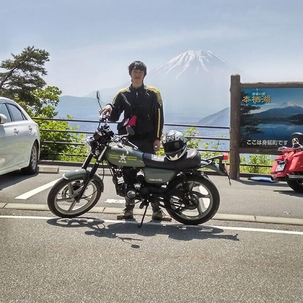 DigiPen (Singapore) alumnus Max Chew poses with a motorcycle, with a mountain in the background
