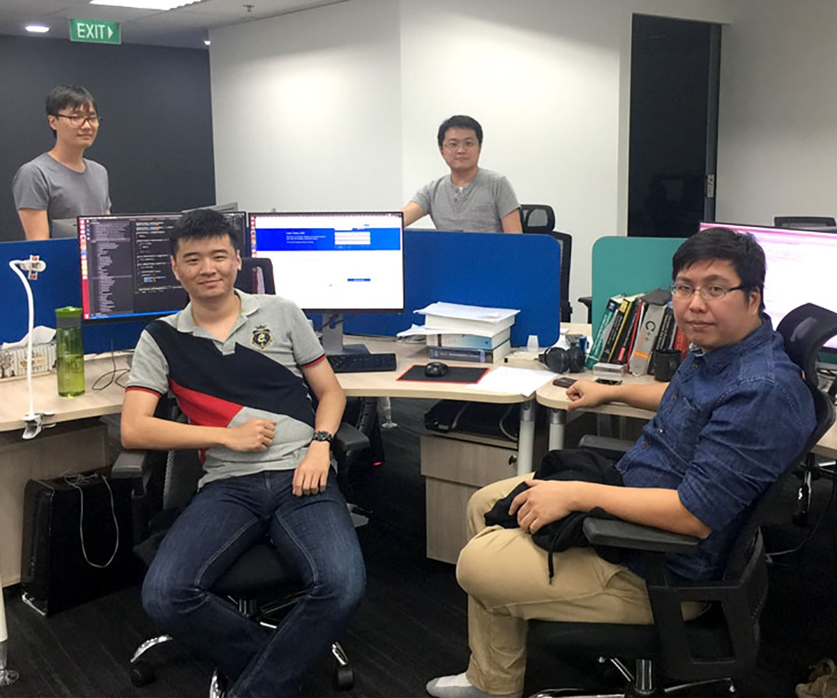 DigiPen Singapore alumni at their desks in the NetVirta office
