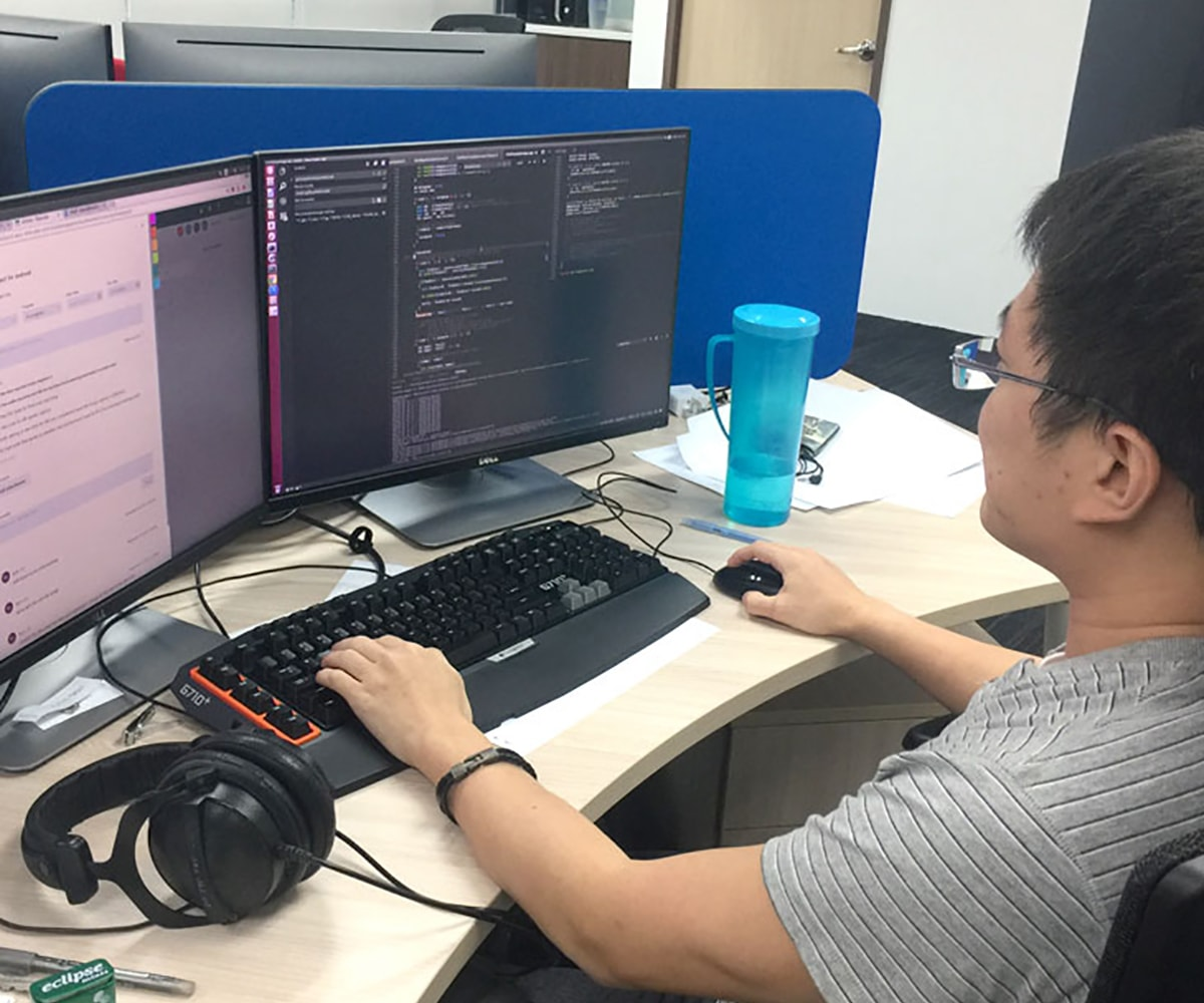 DigiPen Singapore alumnus Ryan Lim works at his desk in the NetVirta office