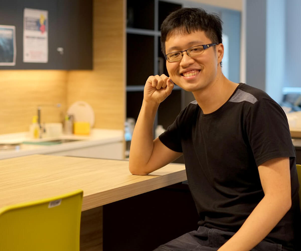 DigiPen graduate Chin Jia Hao smiles sitting at and resting his elbow on a desk