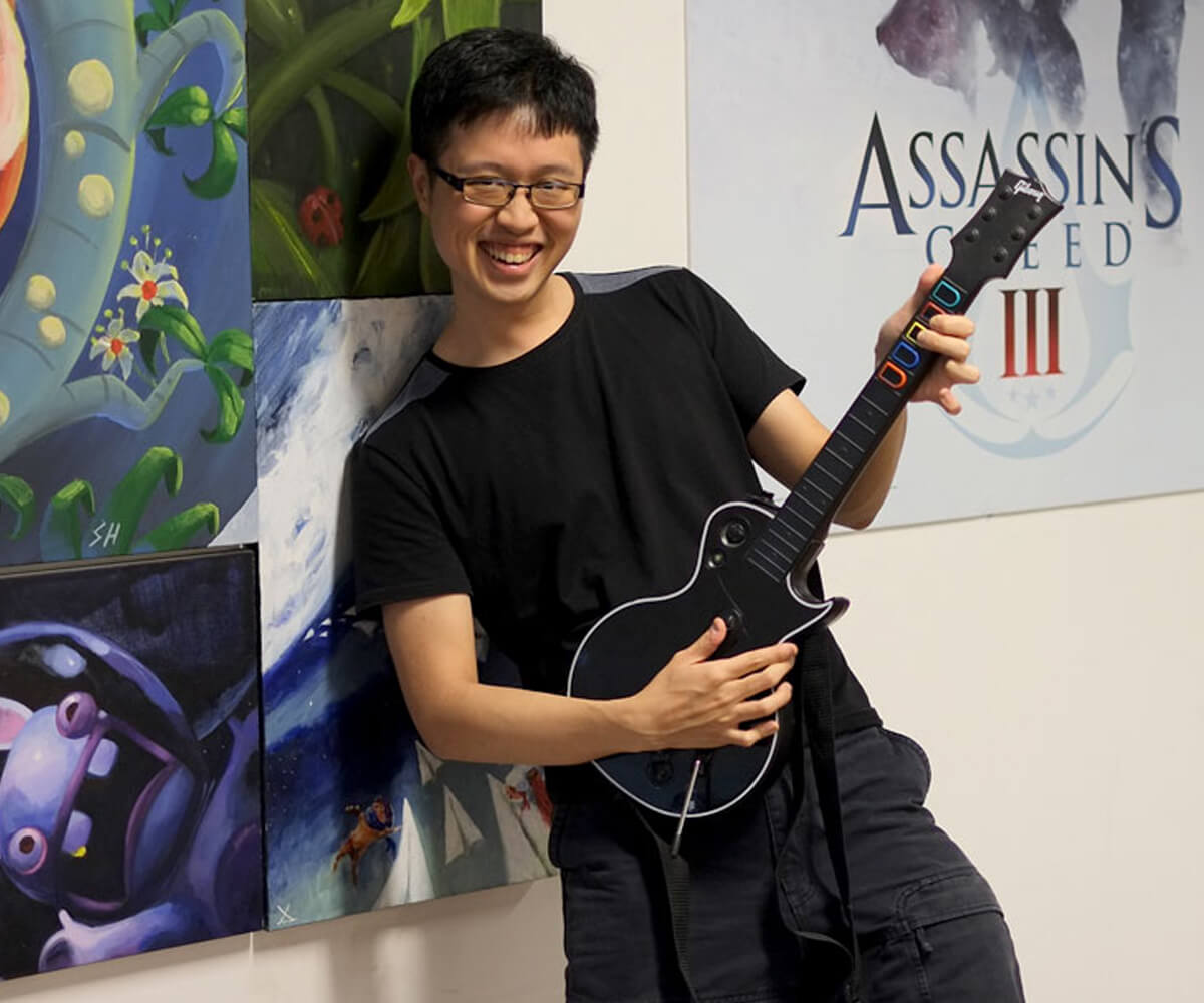 Chin Jia Hao poses smiling holding a black Guitar Hero peripheral. Posters for Assassin's Creed and Rabbids are behind him