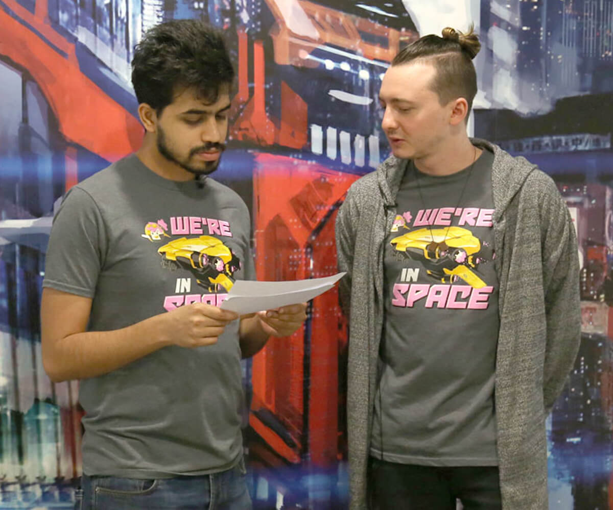 "Two members of Daylight Studios stand in gray t-shirts reading ""We're in Space"" looking at a piece of paper"