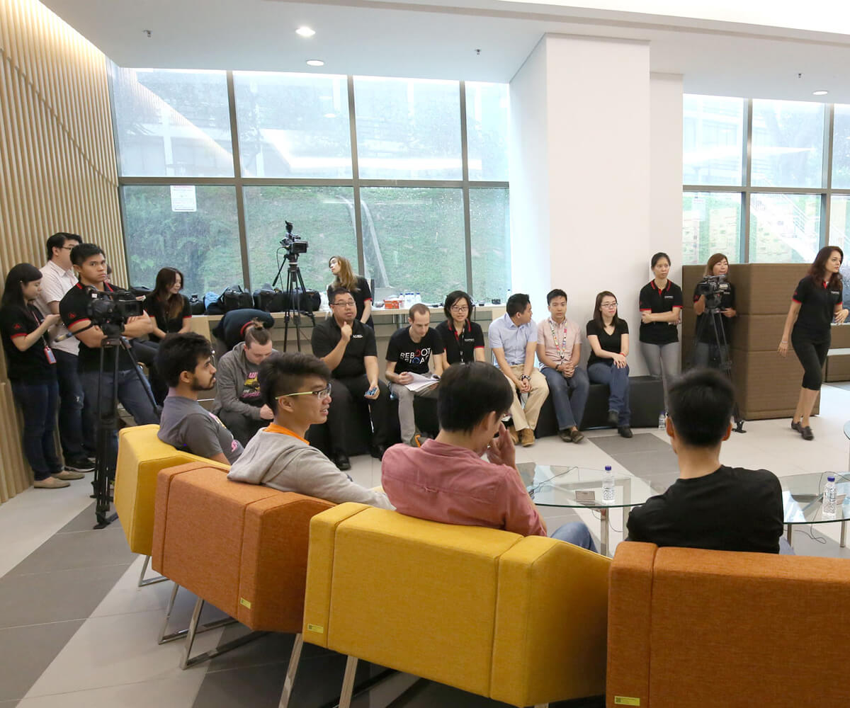Game industry professionals from behind seated in orange and yellow chairs in a foyer being filmed by cameras