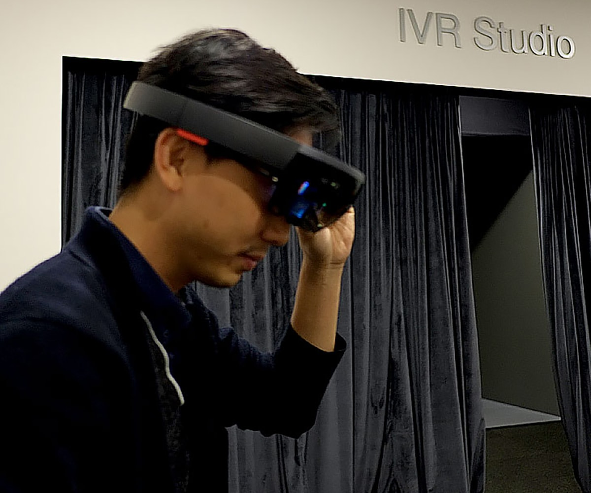 DigiPen (Singapore) alumnus wearing a virtual reality headset in front of a sign that says IVR Studio
