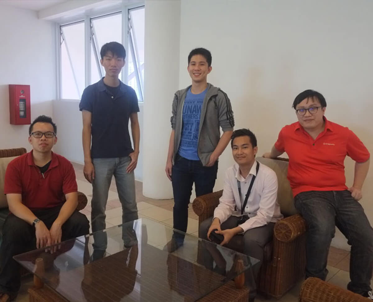 Five DigiPen graduates pose for a photo standing or sitting in a lobby with a glass table