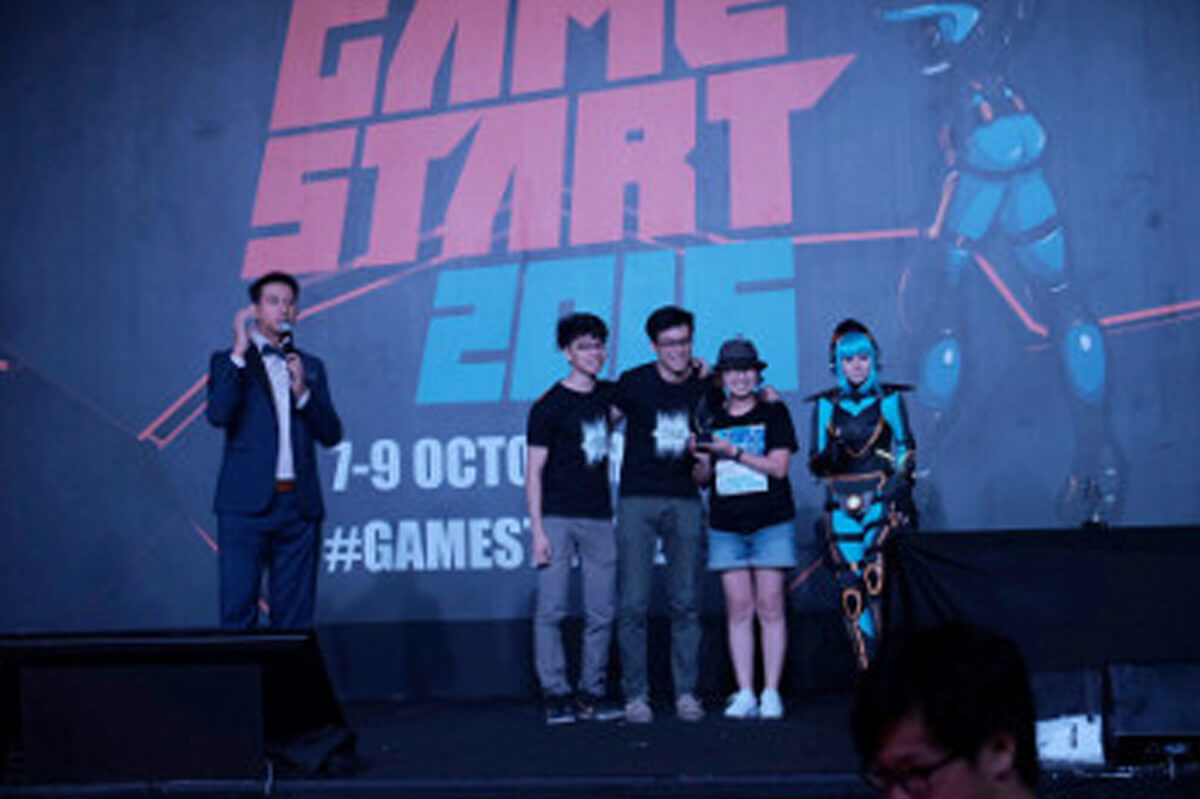 "Three members of the development team standing onstage with emcee and cosplayer. ""Game Start 2016"" on a banner behind them."