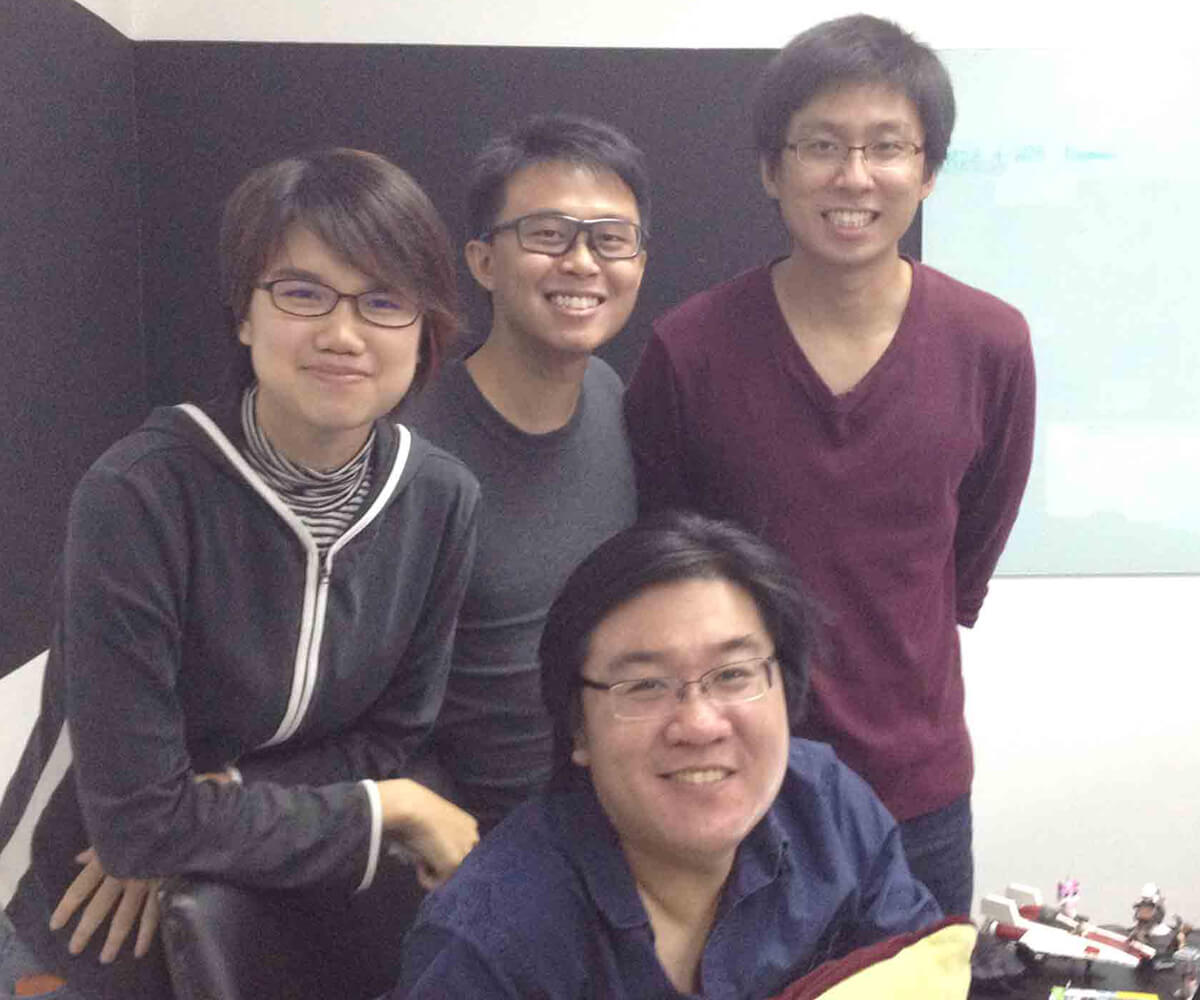 Three graduates stand posing with Creative Director Ian Gregory Tan seated at a desk
