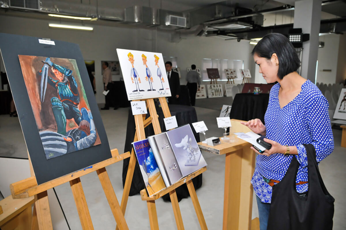 A visitor looks at the paintings, renderings, and other artwork displayed on two easels
