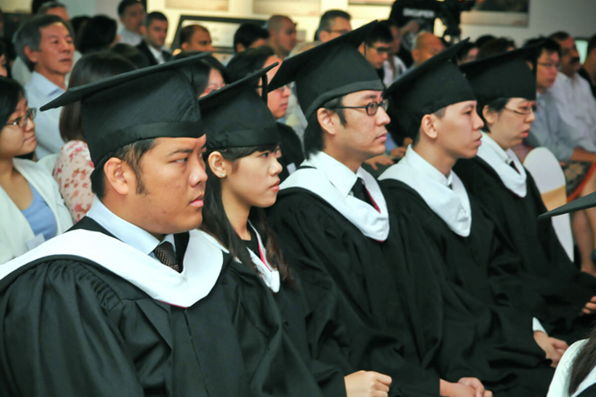Five seated students watch the graduation ceremony in their cap and gowns