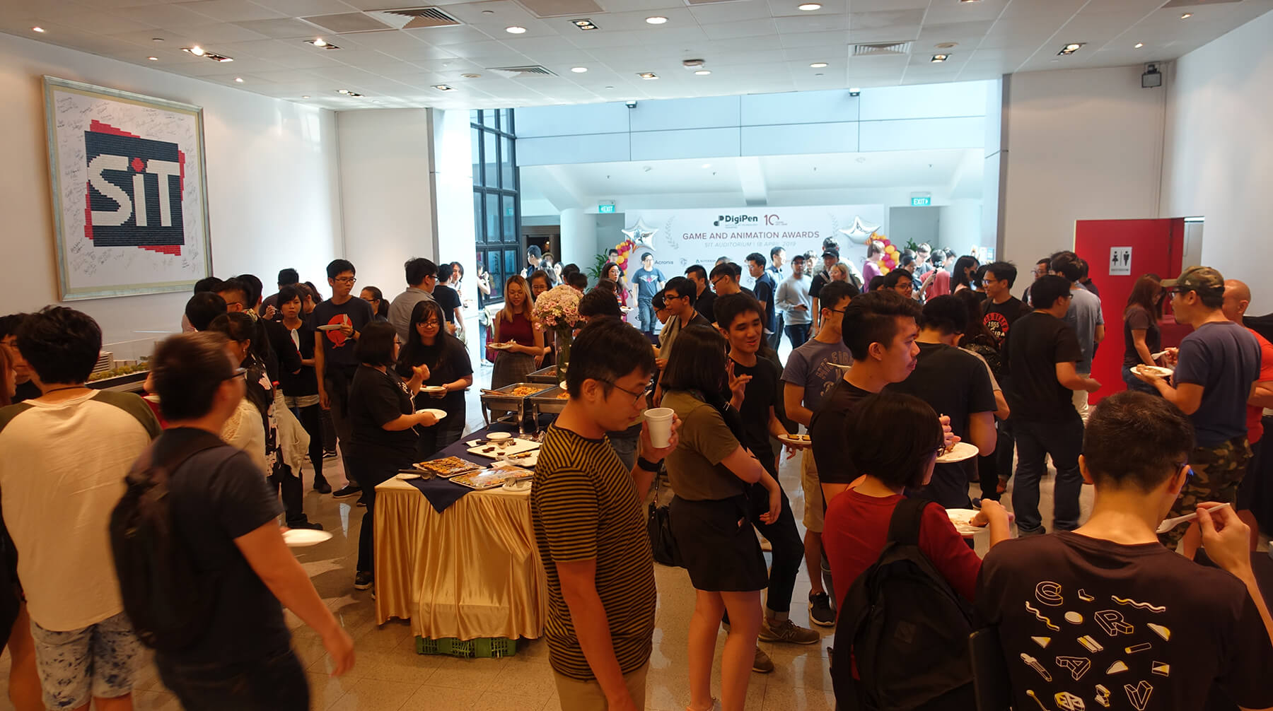 Many students mingle and enjoy refreshments on campus in celebration of the DigiPen Game and Animation Awards.