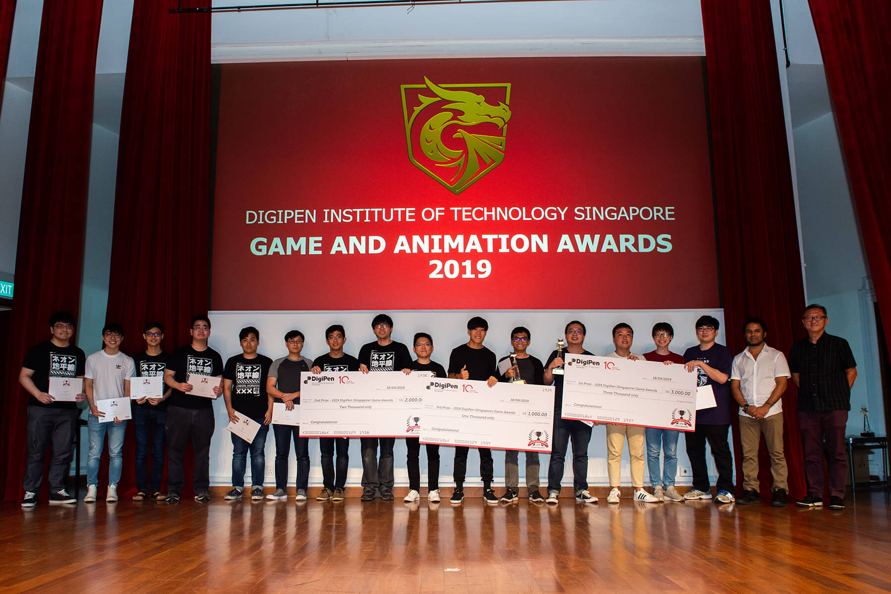 16 students line up in a row to show off their giant checks, certificates, and trophies during the DigiPen Game and Animation Awards show.