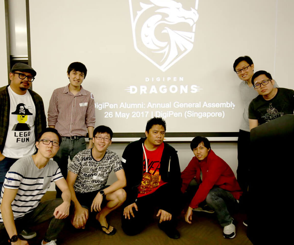 Members of the alumni committee stand in front of a digital projection screen with the DigiPen Dragon logo on it