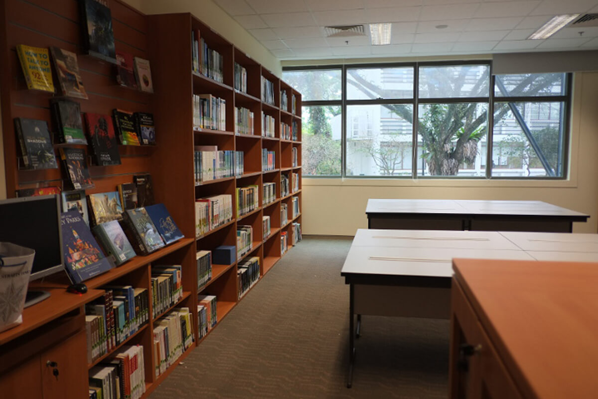Library area with left wall taken up by wooden bookcases full of books. Windows in the far wall, and desks in the center.