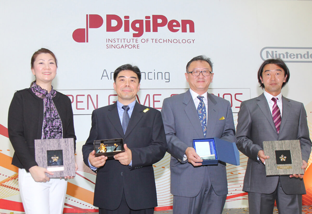 DigiPen Game Studios executives pose for a picture with plaques and awards