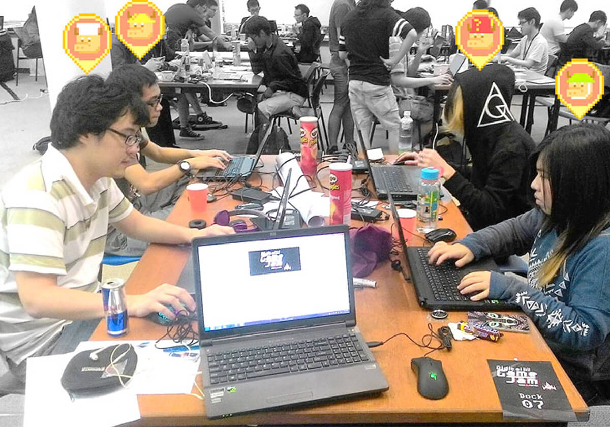 Four students sit at laptops working on their game; pixel-art oxen appear above each team member's head