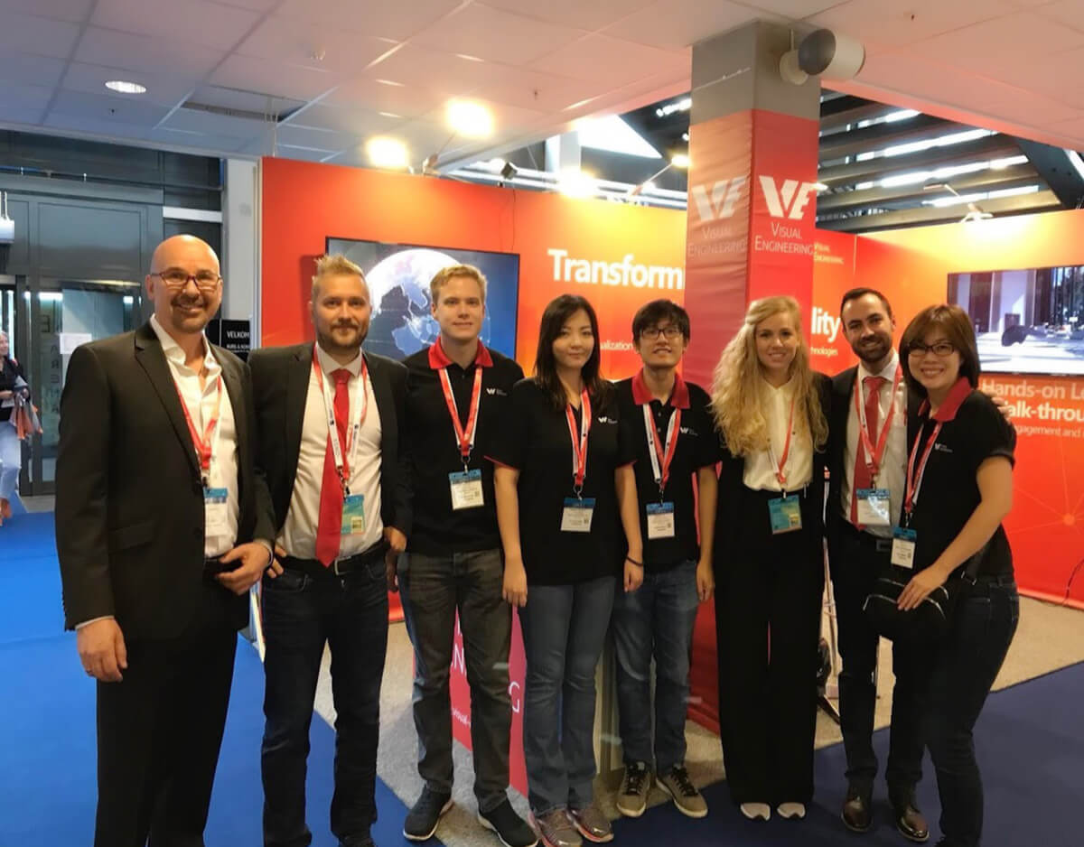 Group photo of 8 Visual Engineering employees standing together and facing camera in front of a company booth during an expo.
