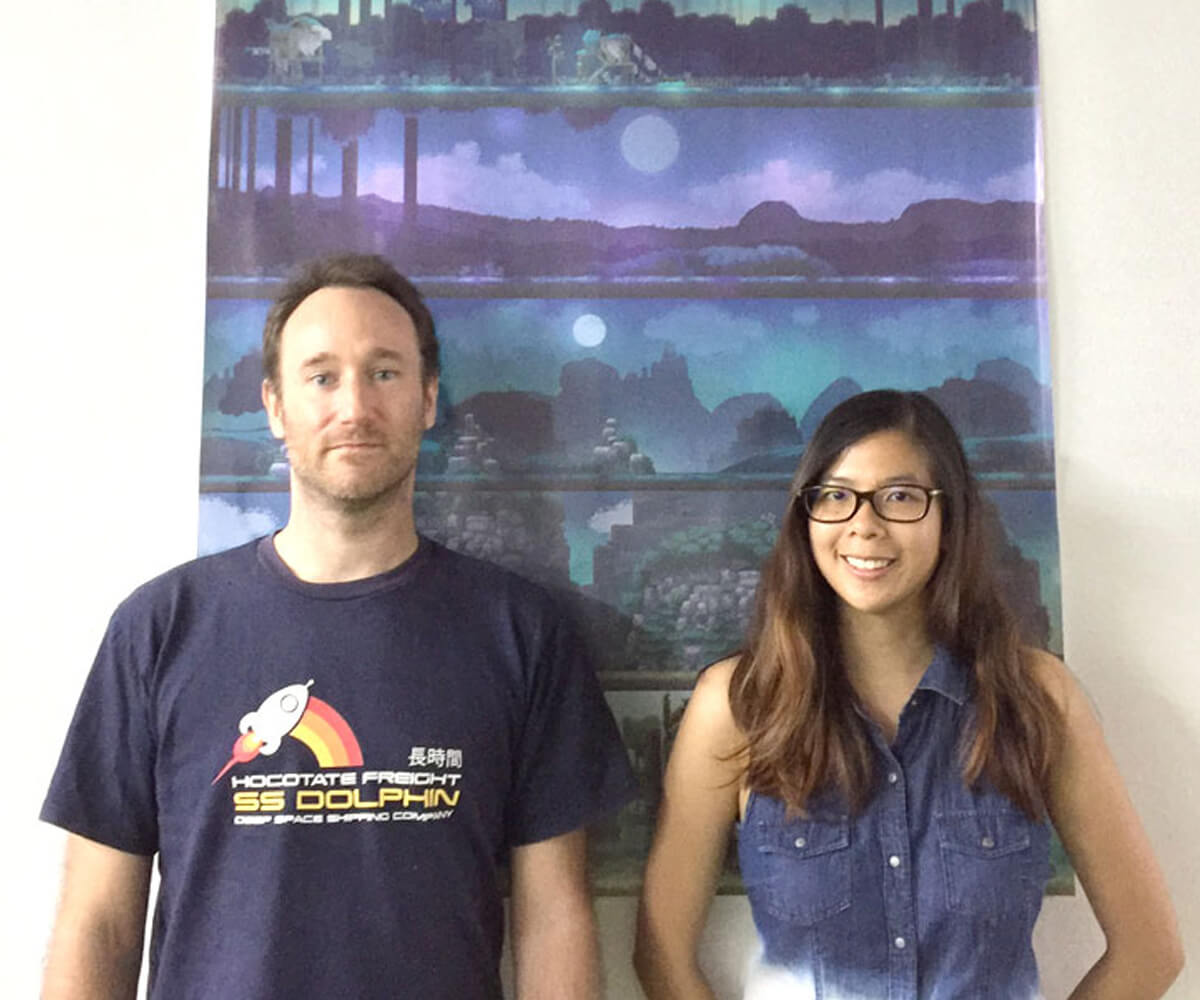 James Barnard and Cindy Lee stand in front a vertical game art tapestry