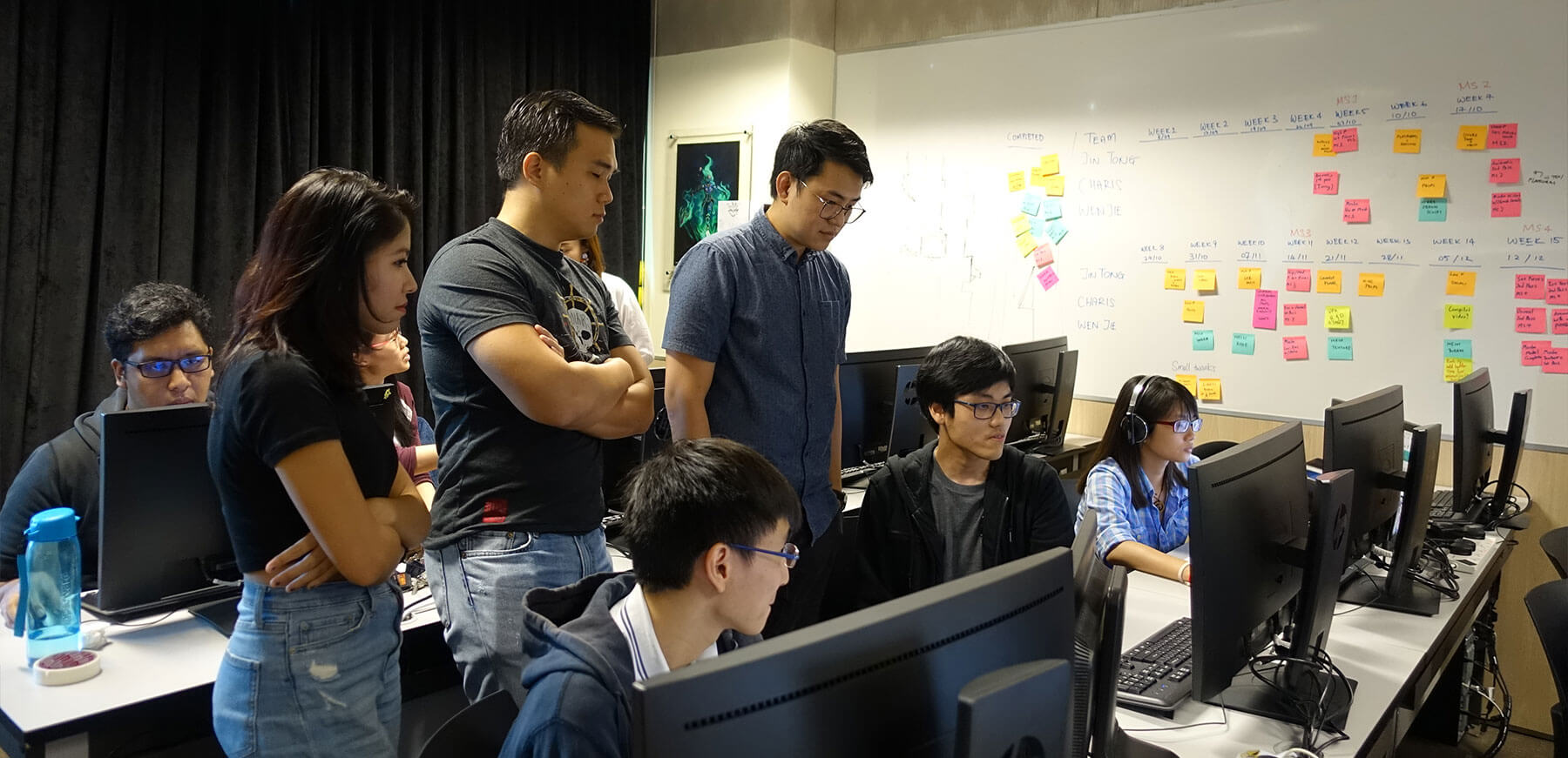Kobe Sek from Ubisoft Singapore and others look down at a student's monitor in a computer lab classroom, with students seated at two rows of workstations.