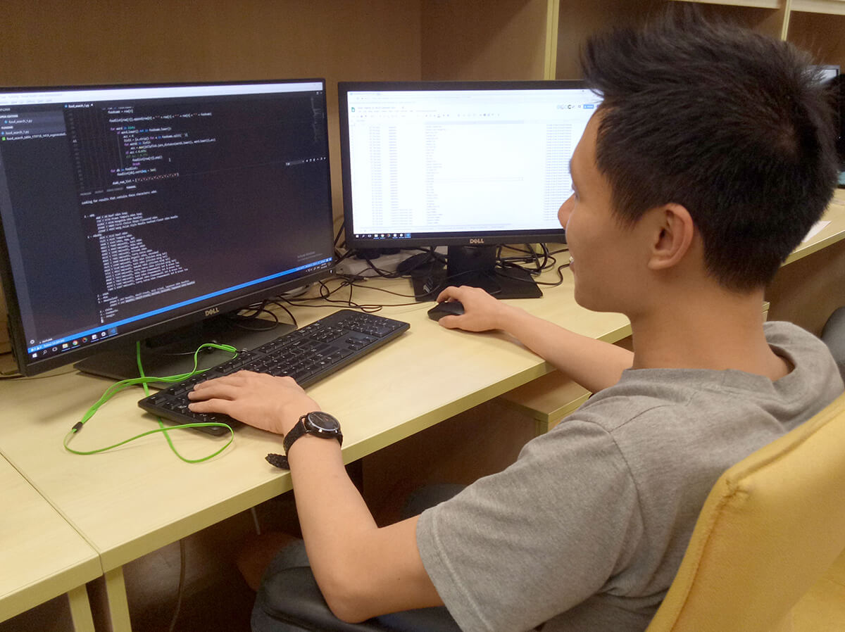 DigiPen (Singapore) BS in Game Design alumnus Lim Sing Gee works at a desk in front of 2 monitors