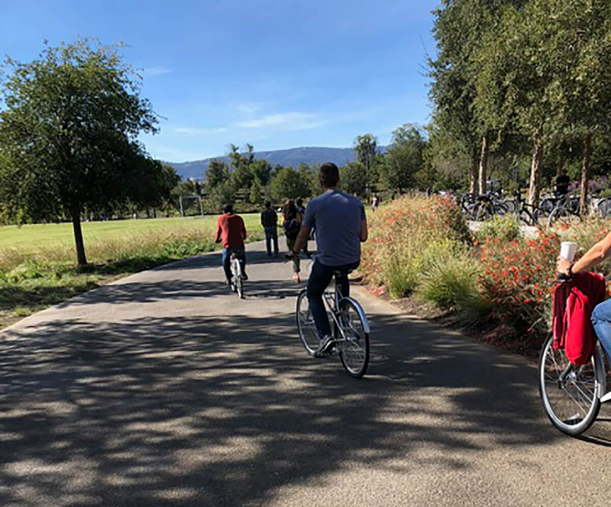Photo of people riding bikes and walking under a clear blue sky along a paved outdoor pathway.